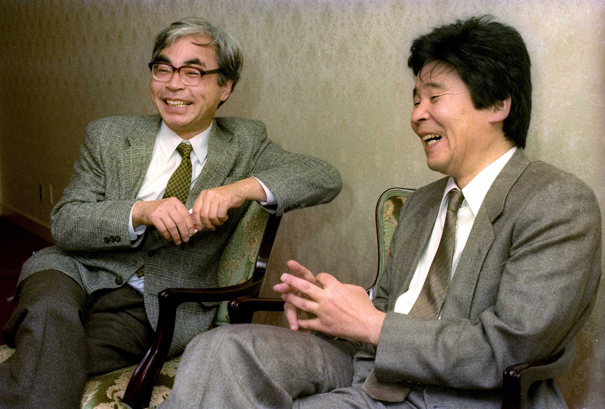 Animated film director Isao Takahata (right) speaks during an interview as his colleague Hayao Miyazaki looks on in November 1990.
