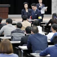 A qualifying exam for applicants hoping to acquire permission to work in the hotel industry using newly available visas is held in the Kasumigaseki district of Tokyo on Sunday. | KYODO