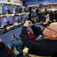 People watch TVs at an electronics store in Tokyo's Yurakucho district Monday as the new Imperial era name, Reiwa, is unveiled by Chief Cabinet Secretary Yoshihide Suga at a televised news conference.  | YOSHIAKI MIURA