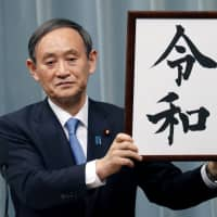 Chief Cabinet Secretary Yoshihide Suga unveils the name of the next era, Reiwa, at the Prime Minister's Office in Tokyo on April 1. | AP