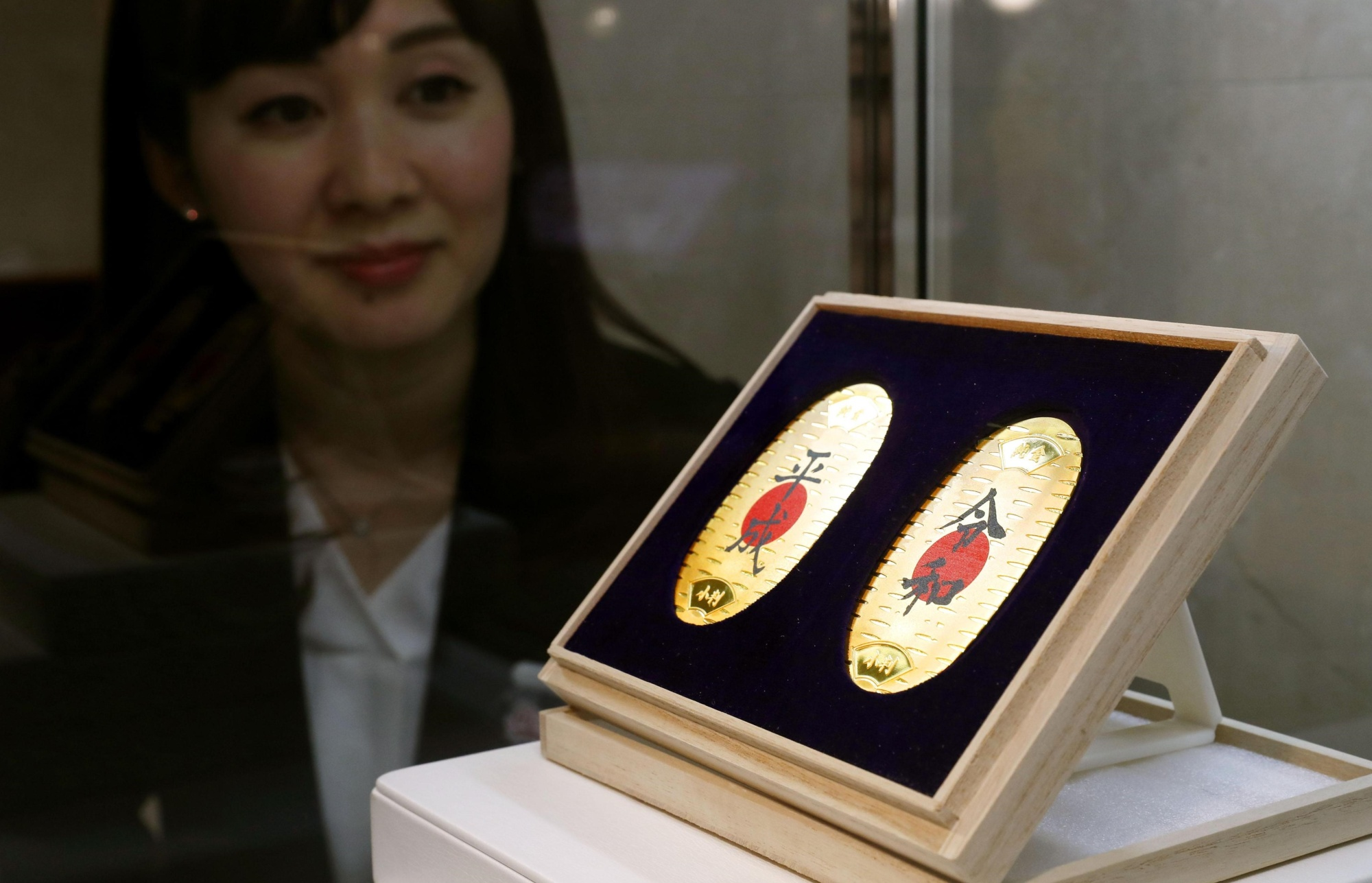 A set of pure gold coins with the current era name, Heisei (left), and the upcoming era name, Reiwa, go on sale for ¥1,296,000 at the Takashimaya department store chain's Nihonbashi branch in Tokyo on Thursday. | KYODO