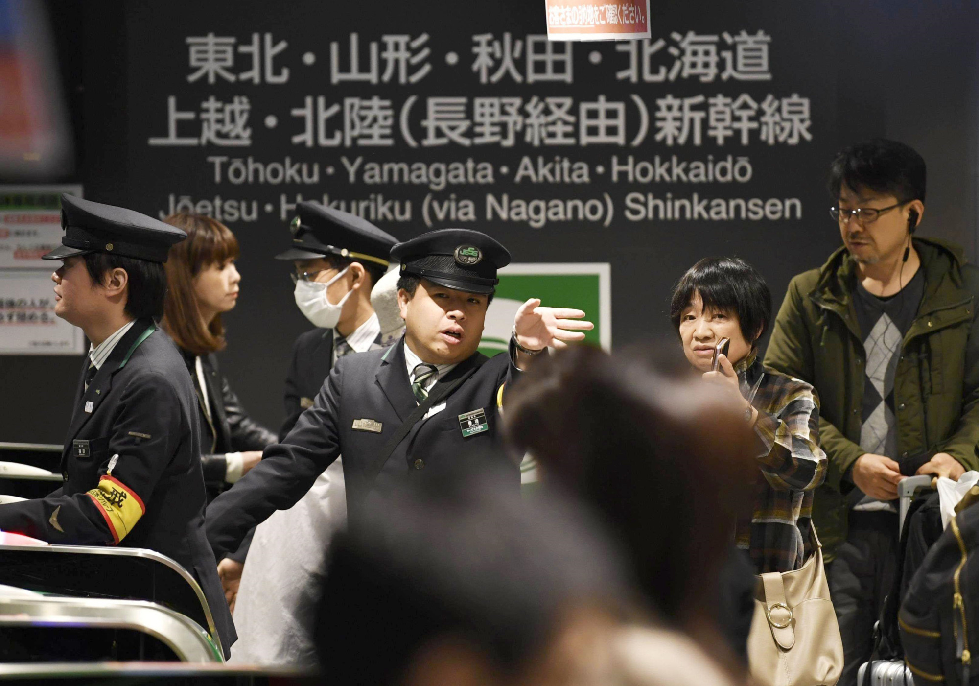 A station worker speaks with a passenger at JR Tokyo Station on Sunday after operations of the Joetsu Shinkansen were temporarily suspended due to a power outrage. | KYODO