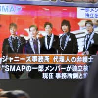 Pedestrians in Tokyo watch a January 2016 news report about pop group SMAP on the verge of breaking up. | KYODO