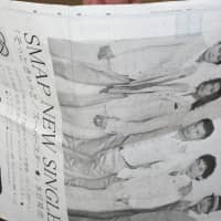 A man reads a four-page newspaper ad for SMAP in Tokyo in August 2009. | BLOOMBERG