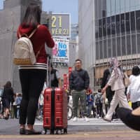 A woman takes a photo at Tokyo's famed Shibuya scramble crossing earlier this month. Many travelers end up sightseeing while dragging along their suitcases because it is often difficult to find an empty coin locker large enough to accommodate big pieces of luggage. | MAGDALENA OSUMI