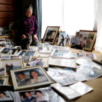 Imperial aficionado Fumiko Shirataki, 78, displays her collection of photographs of imperial family members at her home in Kawasaki on Feb. 21. | REUTERS