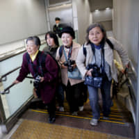Imperial aficionado Fumiko Shirataki, 78, and her friends rush to secure their photo position before the arrival of Crown Prince Naruhito, his wife, Crown Princess Masako, and their daughter, Princess Aiko, at Tokyo Station on March 25. | REUTERS