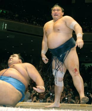 Yokozuna Takanohana reacts after winning against Musashimaru in the championship playoff on the last day of the Summer Grand Sumo Tournament in May 2001. Takanohana overcame a torn meniscus in his right knee, which he suffered two days before, to defeat the Hawaiian yokozuna in dramatic fashion.