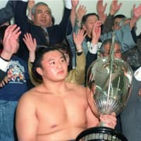 Takahanada, who later became Takanohana, holds a trophy after he won the tournament as the youngest-ever champion in sumo history in January 1992 at Ryogoku Kokugikan.   KYODO