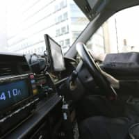 A taxi driver works in Tokyo. A man has been arrested in the city for allegedly robbing over 100 taxis throughout Japan by asking for change before paying and then fleeing with the money. | KYODO