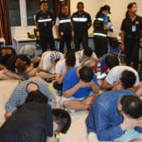 A group of Japanese suspects wait to be taken to a Thai police station after being arrested for fraud in March. | KYODO