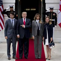Canadian Prime Minister Justin Trudeau stands with U.S. President Donald Trump and their respective spouses in front of the White House in October 2017. | BLOOMBERG
