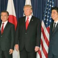 Prime Minister Shinzo Abe, U.S. President Donald Trump and South Korean President Moon Jae-in pose together at the Group of 20 summit in Hamburg, Germany, in July 2017. | KYODO