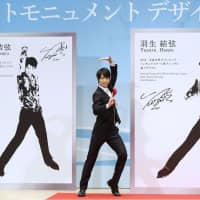 Figure skater Yuzuru Hanyu poses in front of the design of a new monument of him (right) in Sendai on Saturday. | KYODO