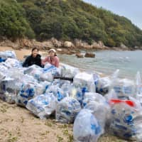 Today's haul: Hana Checketts and Alison Lin, members of the Canadian Academy's Eco Club, pose with the garbage they picked up on a recent trip they led to the shores of Shiraishi Island. | AMY CHAVEZ