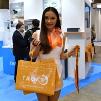 Debbie Kuroda hands out bags containing a notepad and information about PV monitoring service Taoke at the Photovoltaic Power Generation Expo in February. | YOSHIAKI MIURA