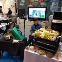 An exhibitor sits beside a display of food products at Tokyo Big Sight in February. | ANDREW MCKIRDY