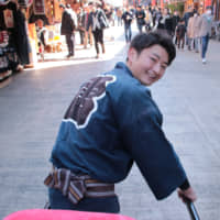 Multitasking: Tatsuhiro Takahashi looks back attentively while pulling a jinrikisha (rickshaw) in Asakusa. | KIT NAGAMURA