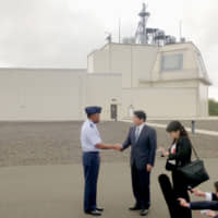 Home front: Defense Minister Itsunori Onodera visits a test complex of the land-based Aegis Ashore missile defense system on the Hawaiian island of Kauai in 2018, ahead of the planned introduction of the U.S.-developed system to Japan. | KYODO