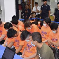 Phone home: Suspected Japanese scammers arrested in Thailand sit at an Immigration Bureau holding center in Bangkok. | KYODO
