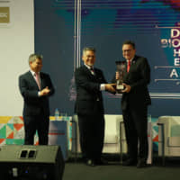 Khalid Abdul Hamid, director of the Ministry of Economic Affairs' Service Industry Section, presents one of  several Halal Excellence Awards that honor various groups' achievements. | WHC