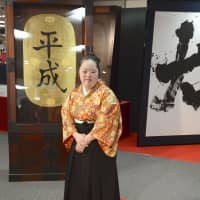The write stuff: A calligrapher stands in front of a piece that reads 'Reiwa,' the new era name. | KYODO