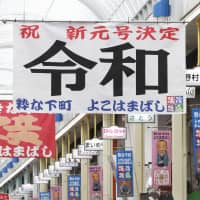 Name day: People in Yokohama pose with banners announcing the new Imperial era name, Reiwa. | KYODO