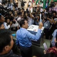 Cambodian Prime Minister Hun Sen holds up his ballot as he prepares to vote in last July's general election. The ruling party won every seat in the national assembly. | BLOOMBERG