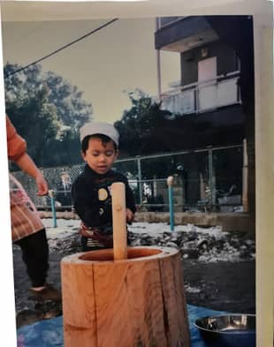 Take a whack: Shinab Shrestha learns about the Japanese tradition of mochi-tsuki — pounding rice into mochi — at his preschool.