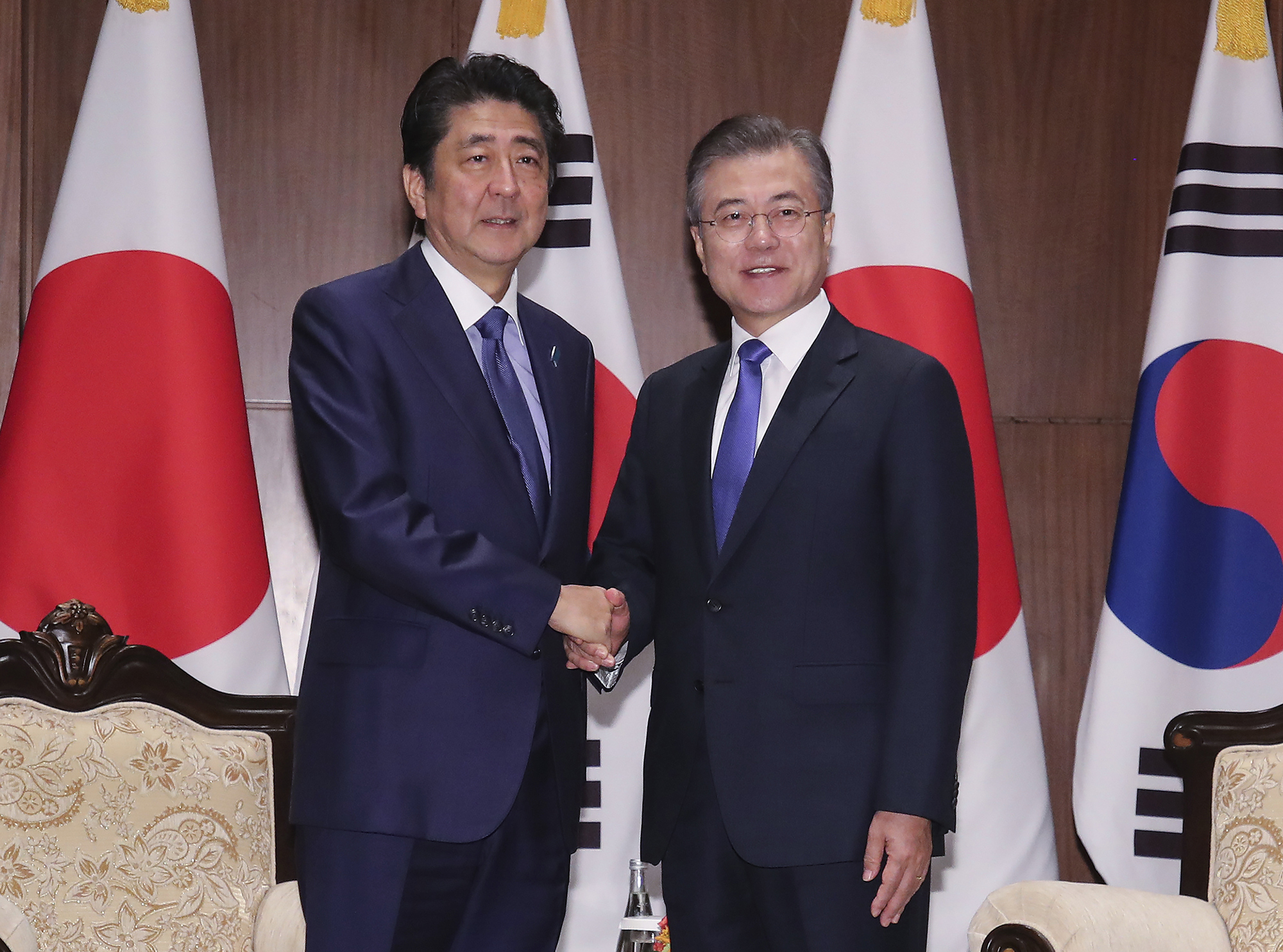 Prime Minister Shinzo Abe and South Korean President Moon Jae-in shake hands in a New York hotel on Sept. 25. The two leaders agreed to promote bilateral relations during their meeting, but since then ties have grown considerably cooler. | AP
