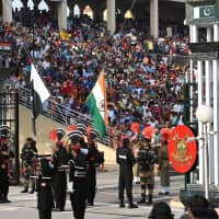 Pakistani Rangers (in black) and Indian Border Security Force personnel perform a flag-lowering ceremony at the Wagah border area between Pakistan and India on Saturday. | AFP-JIJI
