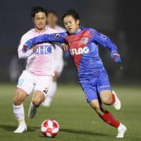 FC Tokyo's Takefusa Kubo (right) competes against Sagan's Yuji Ono during their Levain Cup match on Wednesday night at Prince Chichibu Memorial Rugby Ground. | KYODO
