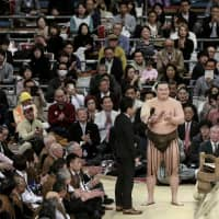 Yokozuna Hakuho leads the crowd in a sanbon-jime cheer after winning the Spring Grand Sumo Tournament on March 24 at Edion Arena Osaka. | KYODO