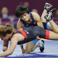 Kaori Icho (top) competes in a women's 57-kg weight class match at the Asian Championships on Friday in Xian, China. | KYODO