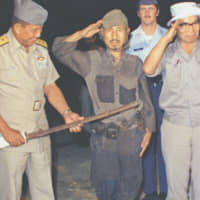 Former Imperial Japanese Army soldier Hiroo Onoda salutes as he hands over his military saber on the Philippine island of Lubang in March 1974, nearly three decades after the end of World War II. | KYODO