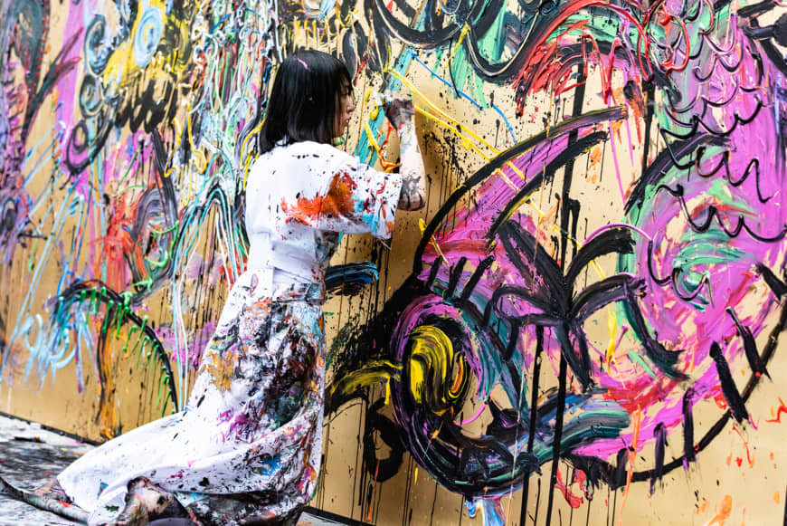 Miwa Komatsu applies colorful acrylic paints on a gilded folding screen during a live painting performance on a stage at the Cleveland Museum of Art on May 11. | TATSUYA AZUMA