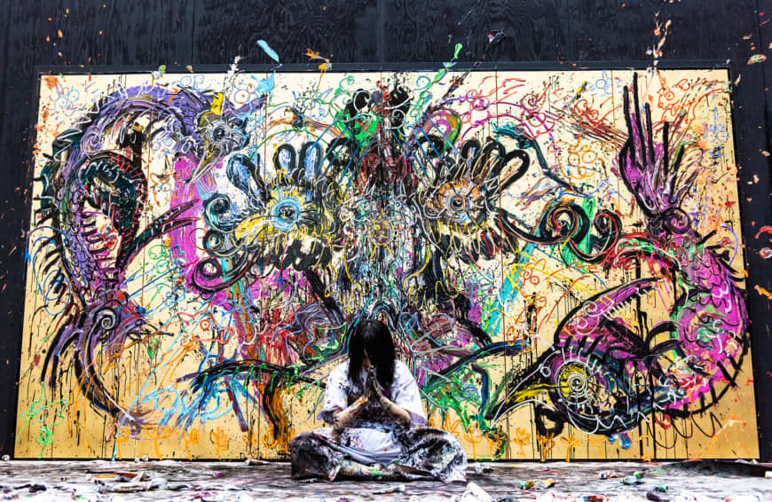 Contemporary artist Miwa Komatsu sits cross-legged and bows to the audience at the end of her live painting performance at the Cleveland Museum of Art on May 11. | TATSUYA AZUMA