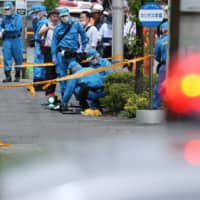 Police forensic experts investigate the scene where a man stabbed 19 people, most of them children, in Kawasaki on Tuesday. | AFP-JIJI