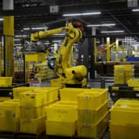 A 6-axis robotic arm picks up sorting containers at the Amazon fulfillment center in Baltimore April 30. | REUTERS