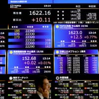 A man walks past a screen displaying share prices in the Osaka Securities Exchange building on April 25. The Topix index has slumped 8.8 percent in the past year. | BLOOMBERG