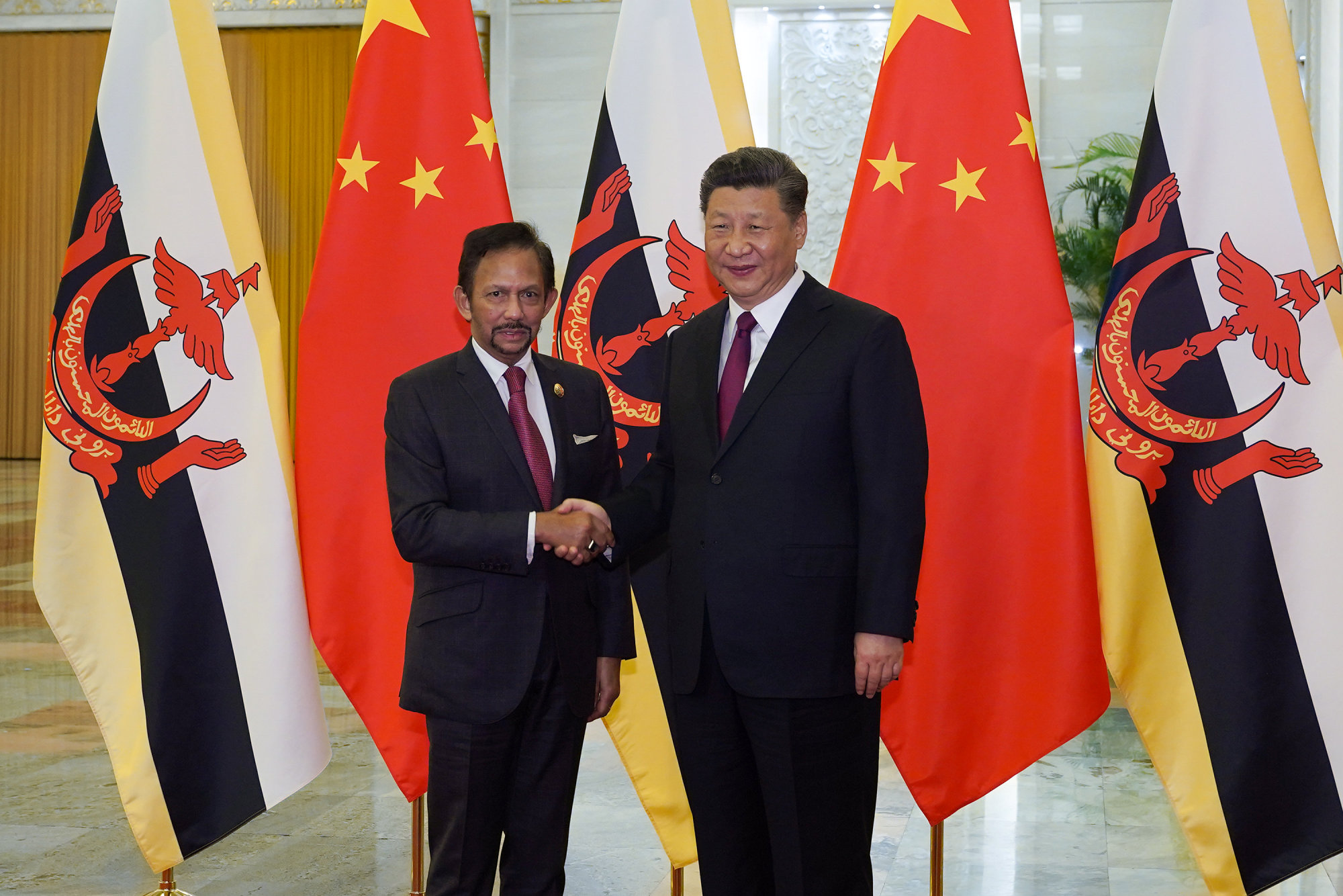 Chinese President Xi Jinping (right) shakes hands with Brunei Sultan Hassanal Bolkiah before the bilateral meeting of the Second Belt and Road Forum at the Great Hall of the People on April 26 in Beijing. | REUTERS