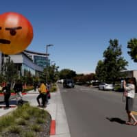 A passerby takes a photograph of an inflatable angry emoji during a protest outside the Facebook 2019 Annual Shareholder Meeting in Menlo Park, California, Thursday. | REUTERS