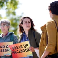 Arielle Cohen (center), a 30-year-old activist from Pittsburgh, holds a sign during a protest outside the Facebook 2019 Annual Shareholder Meeting in Menlo Park, California, Thursday. | REUTERS