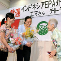 Indonesian caregivers receive flowers during a welcoming ceremony at a home for the elderly in Yokohama on Jan. 29. | KYODO