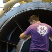 An employee of U.S. multinational General Electric (GE) works on a gas turbine at the GE plant in Belfort, eastern France, in 2015. The American giant GE announced Tuesday it is considering the abolition of more than 1,000 positions in France, mainly in the gas turbine sector and in support services at Belfort and in the Paris region. | AFP-JIJI