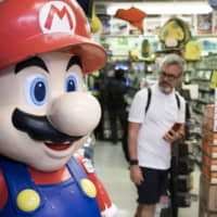 A statue of the Nintendo Co. video-game character Mario stands on display in the Akihabara district of Tokyo. | BLOOMBERG