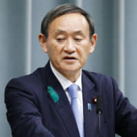 Chief Cabinet Secretary Yoshihide Suga has suggested Japan's three major mobile phone carriers — NTT Docomo Inc., SoftBank Corp. and KDDI Corp. — could reduce their fees by around 40 percent. | KYODO