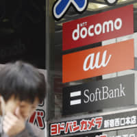 The logos of Japan's three major mobile phone carriers: (from top) NTT Docomo Inc., KDDI Corp.'s au and SoftBank Corp. | KYODO