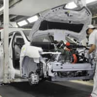 A Nissan Motor Co. Sylphy Zero Emission electric vehicle is assembled at a factory operated by a joint venture with Dongfeng Motor Co. in Guangzhou, China, last Nov. 15.   KYODO