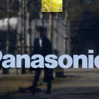 The reflection of a man is seen on a sign showing Panasonic Corp.'s logo, at Panasonic Center in Tokyo on Feb. 2, 2017. | REUTERS